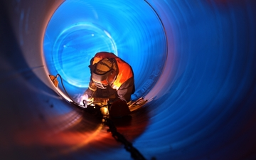 A welder welding in a pipe